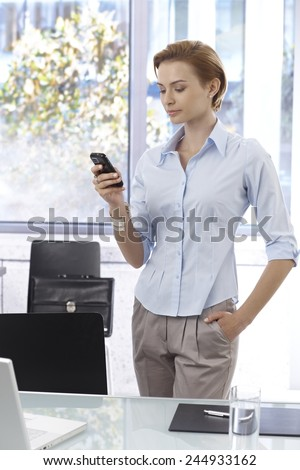 Young businesswoman writing text message on mobilephone, standing at desk with hand in pocket. - stock photo