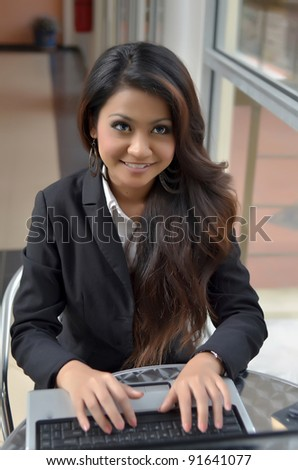 Young businesswomen sharing info on laptop and smile