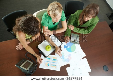 Young businesswomen sitting at table in meeting room, discussing finacial charts. Overhead shot. - stock photo
