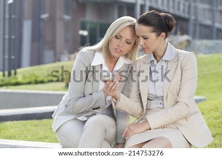 Young businesswomen using mobile phone together while sitting against office building - stock photo