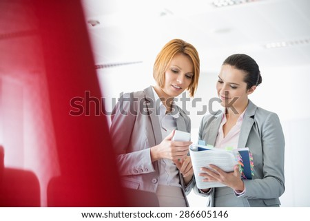 Young businesswomen with book while using cell phone in office - stock photo