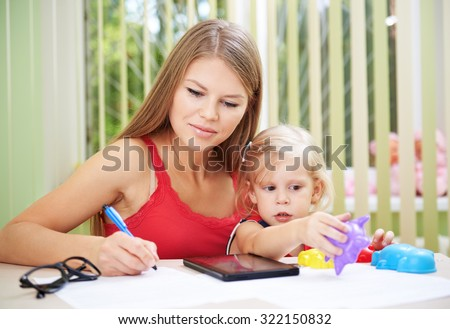 Young busy female telecommuting while her child is playing with toys. Pretty mom with cute daughter checking family bills and documents.  - stock photo