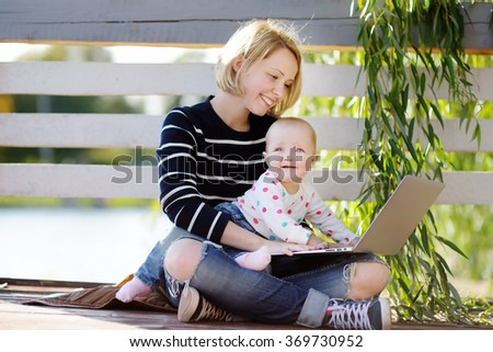 Young busy mother with her adorable baby girl working or studying on laptop in the park