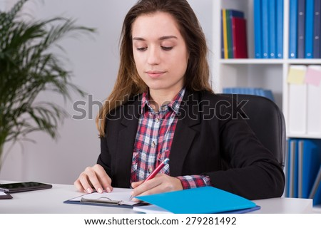 Young busy woman filling documents in office