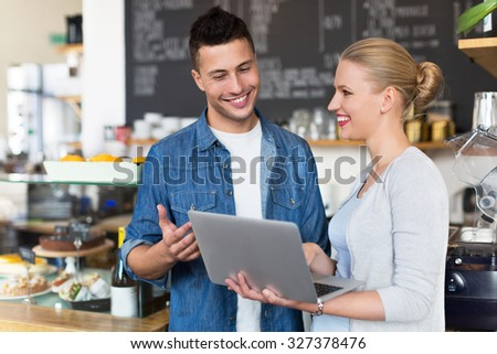 Young cafe owners looking at laptop  - stock photo