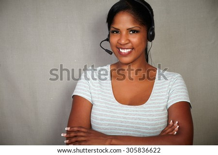 Young call center operator of african ethnicity talking on headset - copy space - stock photo