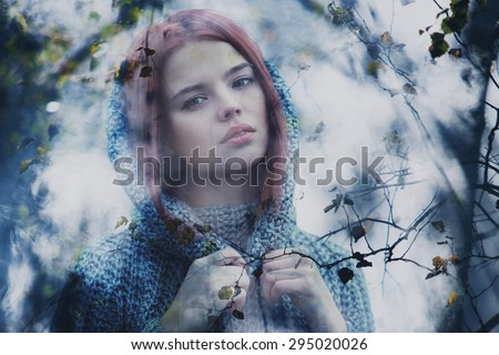 Young calm woman outdoors misty portrait through autumn leaves. - stock photo