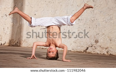 Young capoeria artist performing a headstand on concrete - stock photo