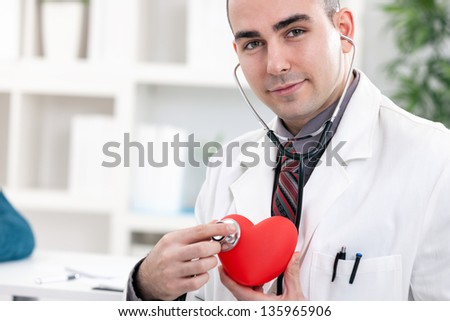 Young cardiologist holding red heart and stethoscope - stock photo