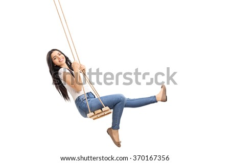 Young carefree girl swinging on a wooden swing and looking at the camera isolated on white background - stock photo