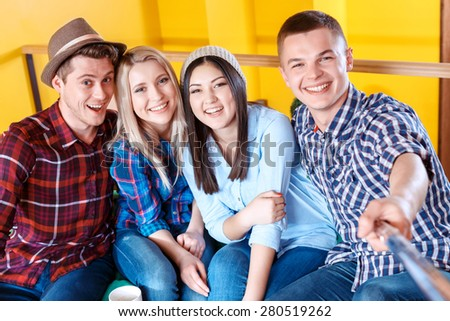 Young carefree happy students wearing casual clothes making photos with a selfie stick and smiling in a yellow room  - stock photo