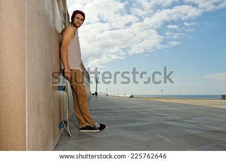 Young, carefree, skateboarder guy, leaning against a granite wall at a beach with his skateboard next to him - stock photo