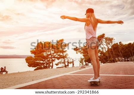 Young carefree woman riding a skateboard along the coast at sunset - stock photo