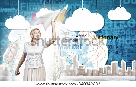 Young carefree woman with paper plane in hands - stock photo