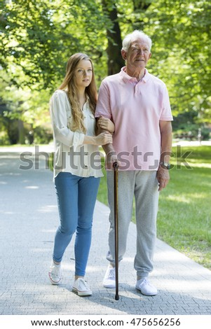 Young carer and elderly man with a walking stick spending time in a park
