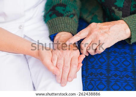 Young carer giving helping hands for elderly woman - stock photo
