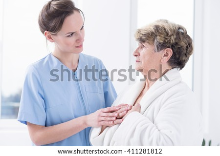 Young carer in blue uniform supporting sad, senior woman, standing in light interior
