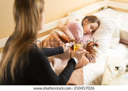 Young caring mother brought hot tea to sleeping sick daughter - stock photo