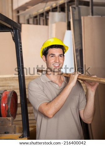 Young carpenter carrying wooden plank on shoulder while looking away in workshop