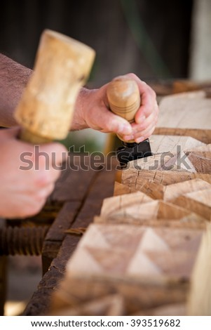 Young carpenter making a traditional hungarian monument, a wooden headboard with his chisel and hammer as a hobby.