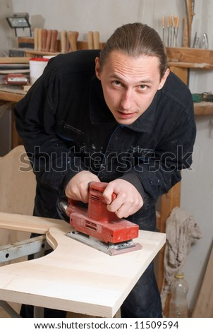 Young carpenter sharoen and polishing part of the door - stock photo