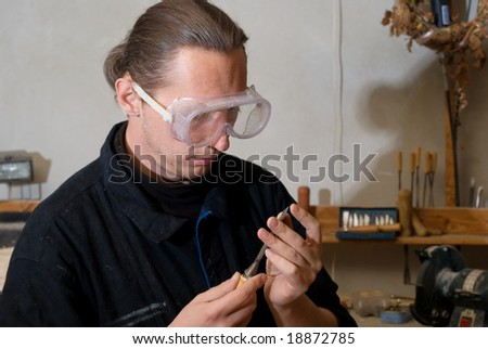 Young carpenter with workglasses checking a sharpen of chisel - stock photo