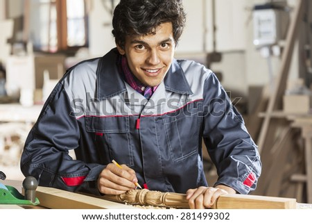 Young carpenter working with cutter in his studio - stock photo