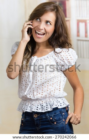 young casual beautiful hispanic woman using her cell phone talking - stock photo