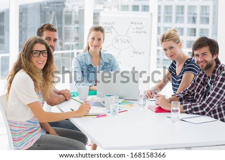 Young casual business people sitting around conference table in a bright office - stock photo