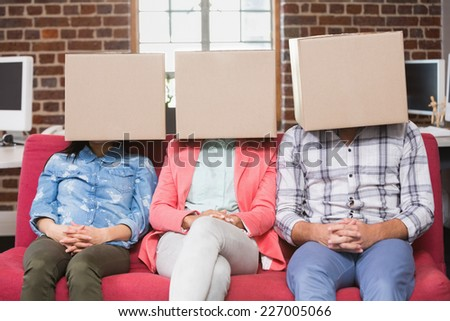 Young casual business team sitting on couch with boxes over heads - stock photo