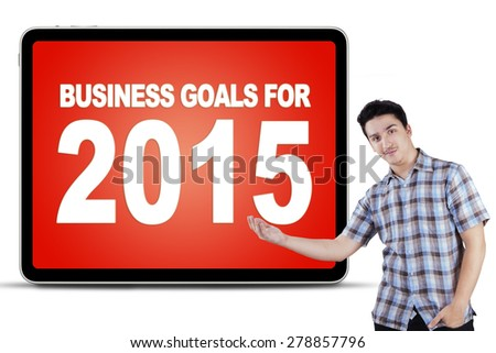 Young casual businessperson showing billboard with business goals for 2015 - stock photo