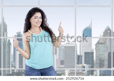 Young casual businesswoman standing near the window and showing thumbs up in the office - stock photo