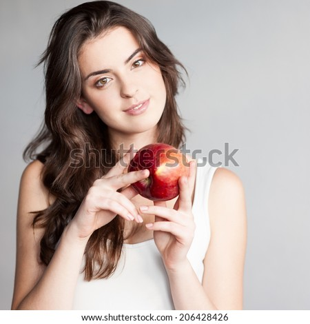 young casual caucasian brunette  woman in white singlet holding red apple over gray background - stock photo