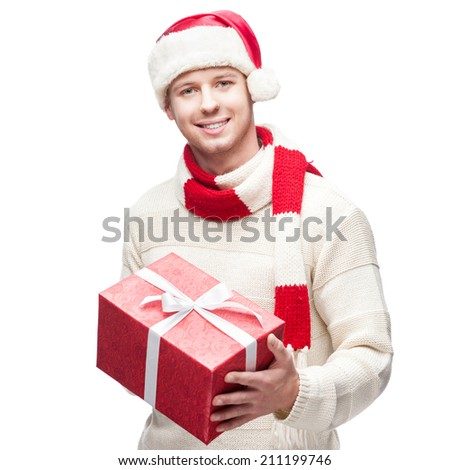 young casual caucasian man in santa hat holding red christmas gift isolated on white background - stock photo