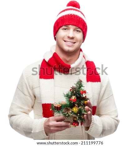 young casual caucasian man in winter hat holding small christmas tree isolated on white background - stock photo