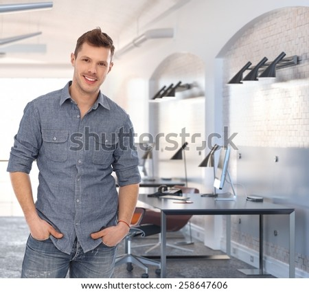Young casual caucasian rookie businessman at creative office. Standing smiling, looking at camera, hand in pocket. - stock photo