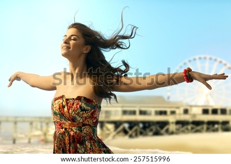Young casual caucasian woman standing eyes closed arms wide open at summer holiday beach. Smiling, dreaming, flying, enjoying freedom. Copyspace. - stock photo