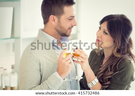 young casual couple cheers with champagne in the kitchen