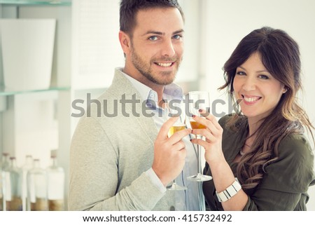 young casual couple cheers with champagne in the kitchen - stock photo