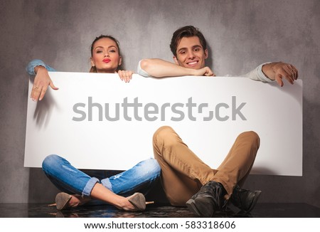 young casual couple laughing and showing a big blank billboard to the camera while sitting on the floor of the studio