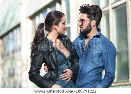 young casual couple looking at each other and smiling while he is embracing her - stock photo