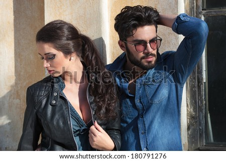 young casual couple looking in different directions, away from the camera. the man is passing his hand through his hair and the woman is holding a hand on her leather jacket