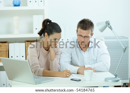 Young casual couple sitting  at desk working together at home office.