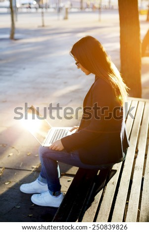 Young casual happy woman typing text on laptop while sitting on wooden bench, hipster girl using laptop outdoors, cross process image - stock photo