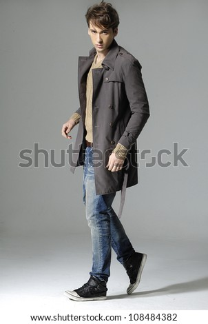 young casual man full body in a gray background - stock photo