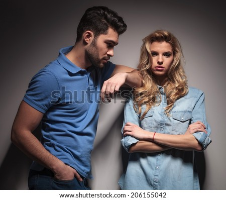 young casual man looking at his girlfriend, studio shot
