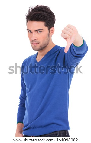young casual man making the thumbs down negative hand sign on white background - stock photo