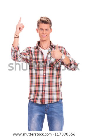 young casual man pointing upward and gesturing thumbs up sign