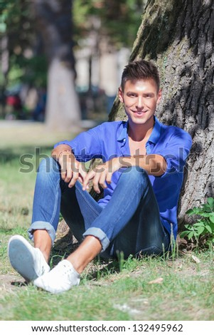 young casual man sitting at the base of a tree in a park and smiling to the camera