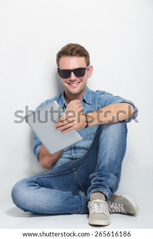 young casual man sitting  holding a tablet and used a sunglasses while smiling to the camera. isolated on white - stock photo